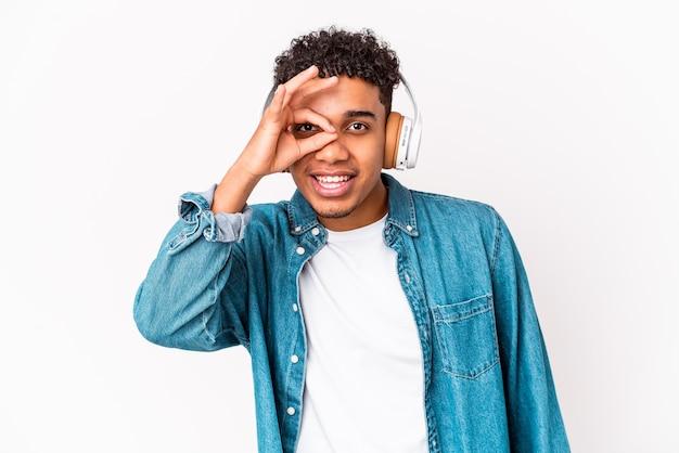 Jonge afro-amerikaanse krullende man geïsoleerd luisteren naar muziek met koptelefoon opgewonden houden ok gebaar op oog.