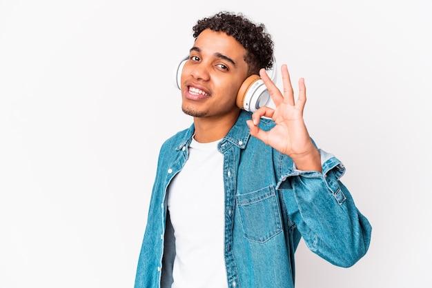 Jonge afro-amerikaanse krullende man geïsoleerd luisteren naar muziek met koptelefoon vrolijk en vol vertrouwen tonen ok gebaar.