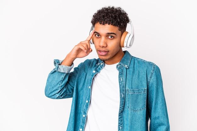 Jonge afro-amerikaanse krullende man geïsoleerd luisteren naar muziek met koptelefoon wijzende tempel met vinger, denken, gericht op een taak.