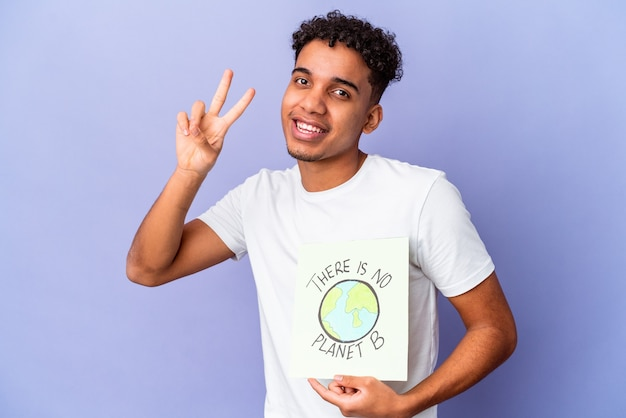 Jonge afro-amerikaanse krullende man geïsoleerd met een er is geen planeet b poster met nummer twee met vingers.