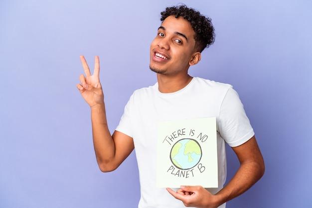 Jonge afro-amerikaanse krullende man geïsoleerd met een er is geen planeet b-poster vrolijk en zorgeloos met een vredessymbool met vingers.