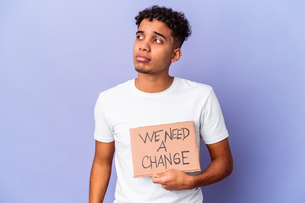 Jonge afro-amerikaanse krullende man geïsoleerd met een we hebben een verandering nodig karton verward, voelt twijfelachtig en onzeker.