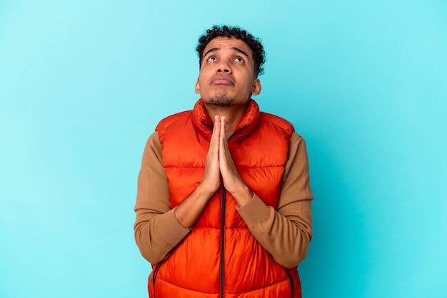 Jonge afro-amerikaanse krullende man geïsoleerd op blauw hand in hand bidden in de buurt van de mond, voelt zich zelfverzekerd.