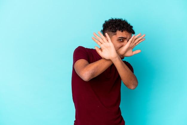 Jonge afro-amerikaanse krullende man geïsoleerd op blauw twee armen gekruist, ontkenning concept.