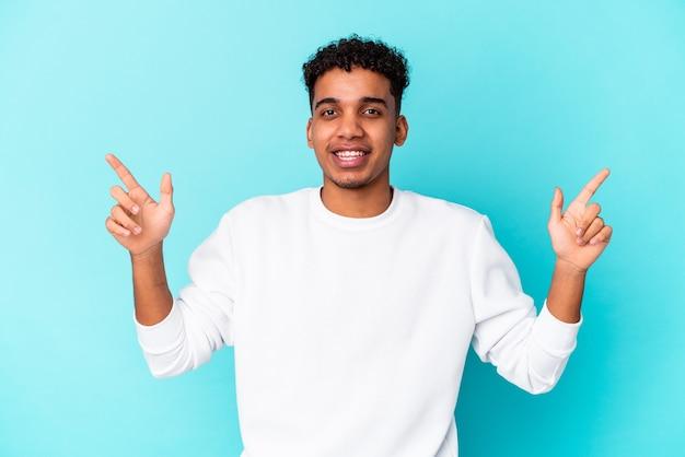 Jonge afro-amerikaanse krullende man geïsoleerd op blauw wijzend naar verschillende kopie ruimtes, een van hen kiezen, tonen met vinger