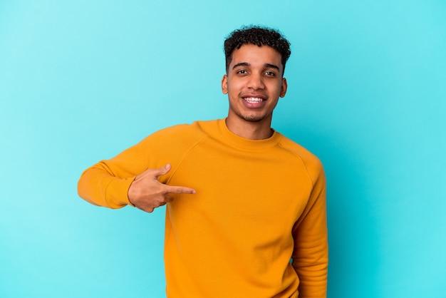 Jonge afro-amerikaanse krullende man geïsoleerd op blauwe persoon met de hand wijzend naar een shirt kopie ruimte, trots en zelfverzekerd