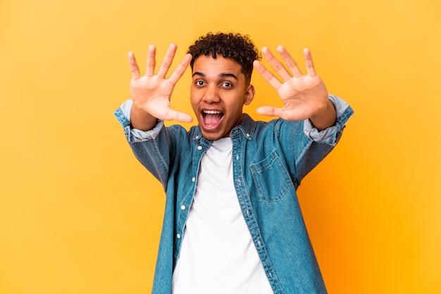 Jonge afro-amerikaanse krullende man geïsoleerd op paars met nummer tien met handen.