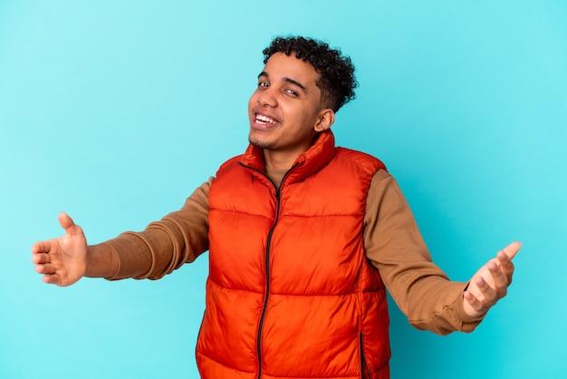 Jonge afro-amerikaanse krullende man op blauw met een welkome uitdrukking.
