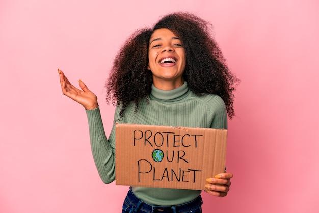 Jonge afro-amerikaanse krullende vrouw die een aangename verrassing ontvangt, opgewonden en handen opheft.