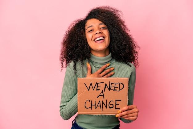 Jonge afro-amerikaanse krullende vrouw die een kartonnen doos met een wisselgeld vasthoudt, lacht hardop terwijl hij de hand op de borst houdt.