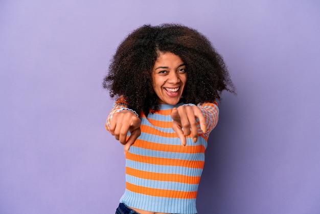 Jonge afro-amerikaanse krullende vrouw geïsoleerd op paarse vrolijke glimlachen naar voren wijzen.