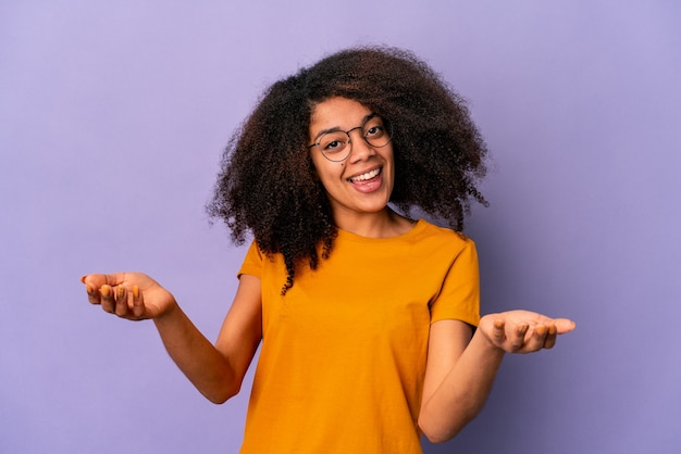 Jonge afro-amerikaanse krullende vrouw op paars met een welkome uitdrukking.