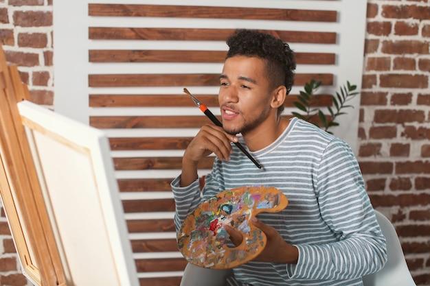 Jonge afro-amerikaanse kunstenaar schildert foto in werkplaats