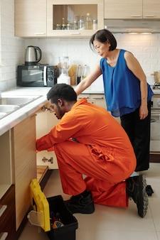 Jonge afro-amerikaanse loodgieter in oranje bodysuit die pijp in de keuken installeert terwijl een volwassen vrouw toezicht houdt op het proces