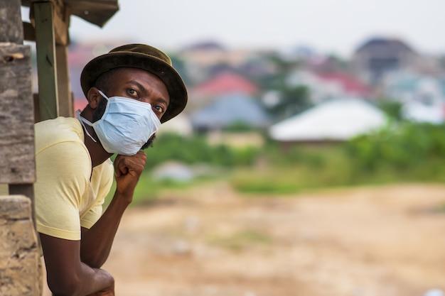 Jonge afro-amerikaanse man die achter een hek staat met een beschermend gezichtsmasker
