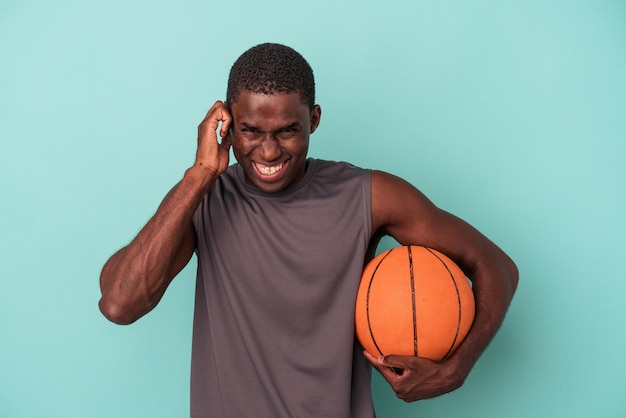Jonge afro-amerikaanse man die basketbal speelt geïsoleerd op een blauwe achtergrond die oren bedekt met handen.