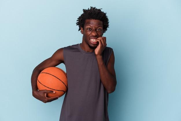 Jonge afro-amerikaanse man die basketbal speelt geïsoleerd op een blauwe achtergrond, vingernagels bijt, nerveus en erg angstig.