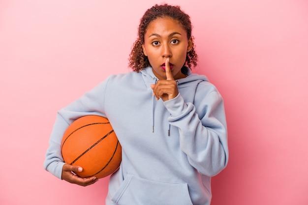 Jonge afro-amerikaanse man die basketbal speelt geïsoleerd op een roze achtergrond die een geheim houdt of om stilte vraagt.