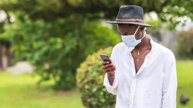 Jonge afro-amerikaanse man die een beschermend gezichtsmasker draagt en zijn telefoon buitenshuis gebruikt