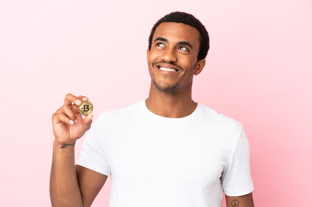 Jonge afro-amerikaanse man die een bitcoin over een geïsoleerde roze muur houdt en een idee denkt terwijl hij omhoog kijkt