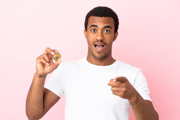 Jonge afro-amerikaanse man die een bitcoin over geïsoleerde roze achtergrond vasthoudt, verrast en naar voren wijst