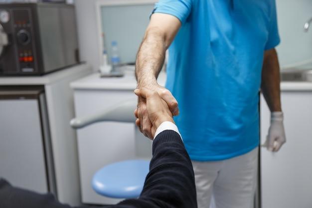 Jonge afro-amerikaanse man die hand van tandarts schudt die bezoek in medische kliniek heeft.