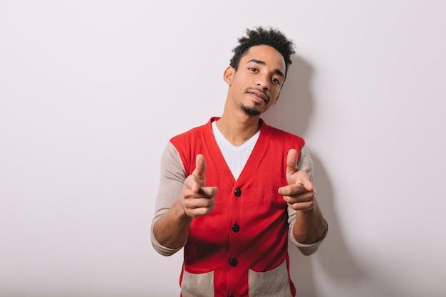 Jonge afro-amerikaanse man die zich voordeed op een witte muur en vredesteken met geconcentreerde emoties op grijs vertoont