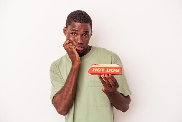 Jonge afro-amerikaanse man eet een hotdog geïsoleerd op een witte achtergrond bijtende nagels, nerveus en erg angstig.