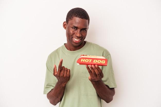 Jonge afro-amerikaanse man eet een hotdog geïsoleerd op een witte achtergrond en wijst met de vinger naar je alsof uitnodigend dichterbij komt.