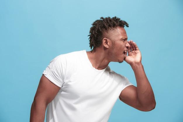 Jonge afro-amerikaanse man fluistert een geheim achter haar hand over blauw