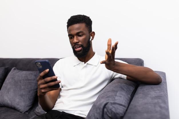 Jonge afro-amerikaanse man gebaar tijdens het praten aan de telefoon via airpods zittend op de bank