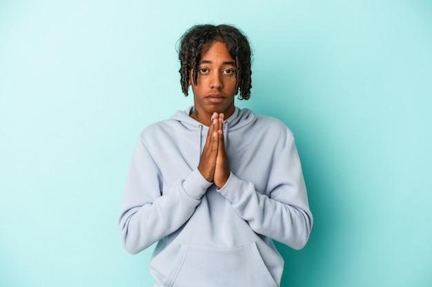 Jonge afro-amerikaanse man geïsoleerd op blauwe achtergrond bidden, tonen toewijding, religieuze persoon op zoek naar goddelijke inspiratie.