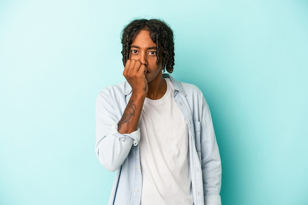 Jonge afro-amerikaanse man geïsoleerd op blauwe achtergrond bijtende vingernagels, nerveus en erg angstig.