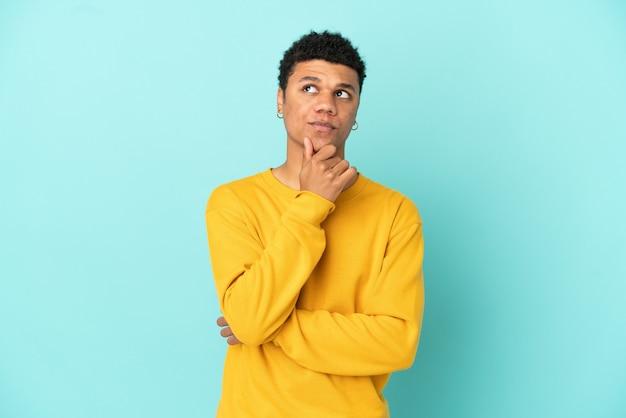 Jonge afro-amerikaanse man geïsoleerd op blauwe achtergrond die een idee denkt terwijl hij omhoog kijkt
