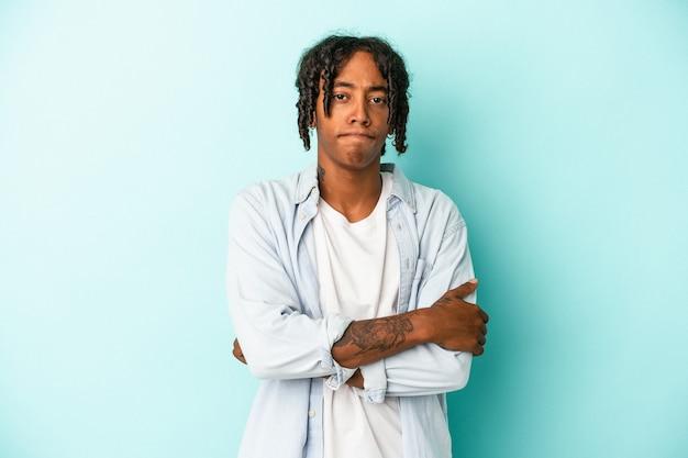 Jonge afro-amerikaanse man geïsoleerd op blauwe achtergrond fronsend gezicht in ongenoegen, houdt armen gevouwen.