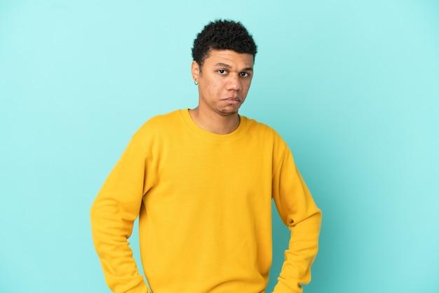 Jonge afro-amerikaanse man geïsoleerd op blauwe achtergrond met droevige uitdrukking