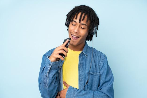 Jonge afro-amerikaanse man geïsoleerd op blauwe muziek luisteren met een mobiel en zingen