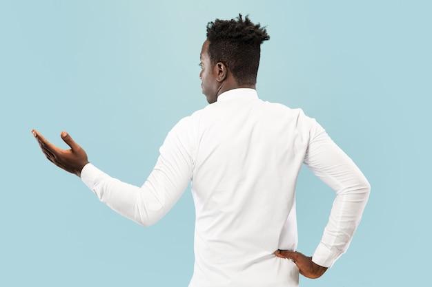 Jonge afro-amerikaanse man geïsoleerd op blauwe studio achtergrond, lichaamsuitdrukking. mooi mannelijk halflang portret geschoten van achteren. concept van menselijke emoties, gezichtsuitdrukking.