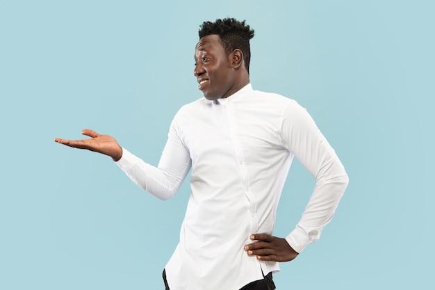 Jonge afro-amerikaanse man geïsoleerd op blauwe studio achtergrond