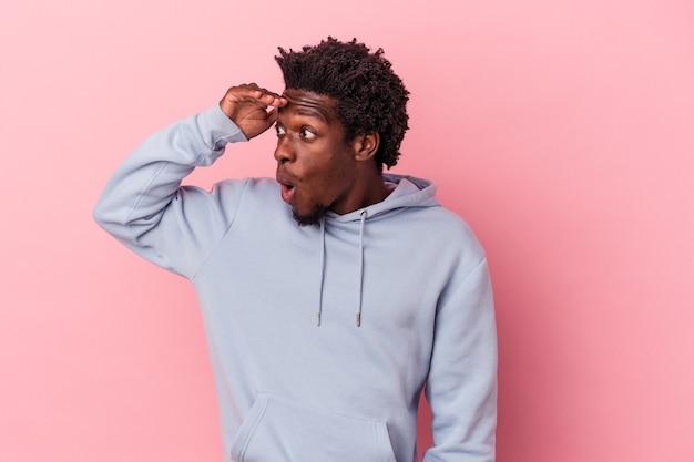 Jonge afro-amerikaanse man geïsoleerd op een roze achtergrond die ver weg kijkt en hand op het voorhoofd houdt.