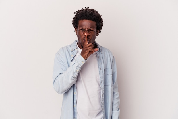 Jonge afro-amerikaanse man geïsoleerd op een witte achtergrond die een geheim houdt of om stilte vraagt.