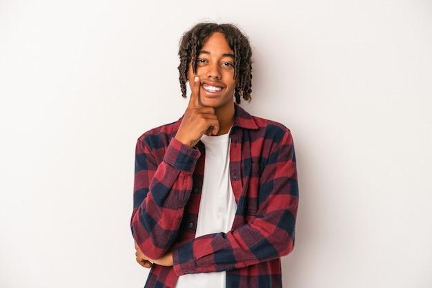 Jonge afro-amerikaanse man geïsoleerd op een witte achtergrond glimlachend gelukkig en zelfverzekerd, kin met de hand aan te raken.