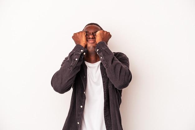 Jonge afro-amerikaanse man geïsoleerd op een witte achtergrond huilen, ongelukkig met iets, pijn en verwarring concept.