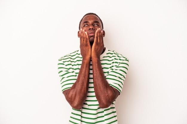 Jonge afro-amerikaanse man geïsoleerd op een witte achtergrond jammerend en huilend troosteloos.