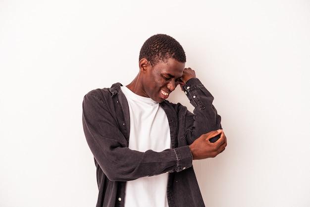 Jonge afro-amerikaanse man geïsoleerd op een witte achtergrond masseren elleboog, lijden na een slechte beweging.