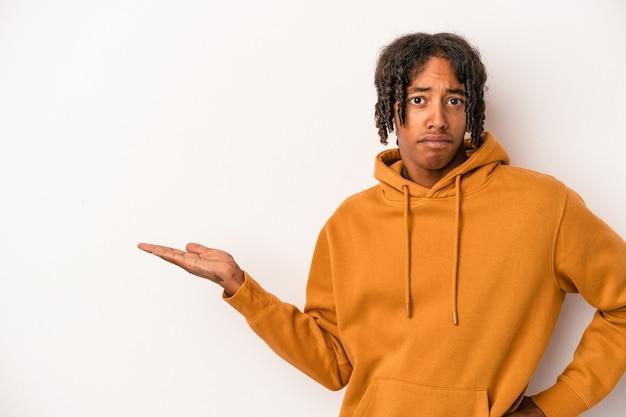 Jonge afro-amerikaanse man geïsoleerd op een witte achtergrond met een kopie ruimte op een palm en met een andere hand op de taille.