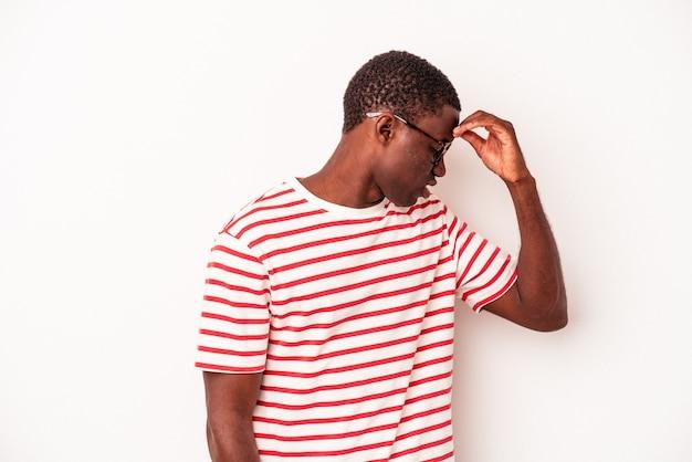 Jonge afro-amerikaanse man geïsoleerd op een witte achtergrond met hoofdpijn, aanraken van de voorkant van het gezicht.