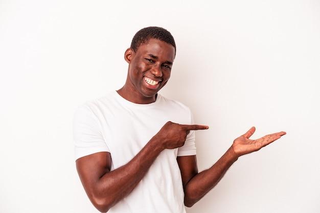 Jonge afro-amerikaanse man geïsoleerd op een witte achtergrond opgewonden met een kopie ruimte op de palm.