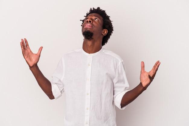 Jonge afro-amerikaanse man geïsoleerd op een witte achtergrond schreeuwen naar de hemel, opzoeken, gefrustreerd.