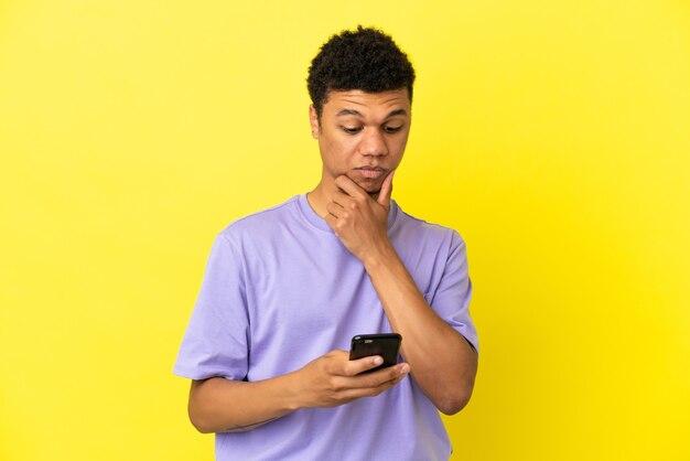 Jonge afro-amerikaanse man geïsoleerd op gele achtergrond denken en een bericht verzenden